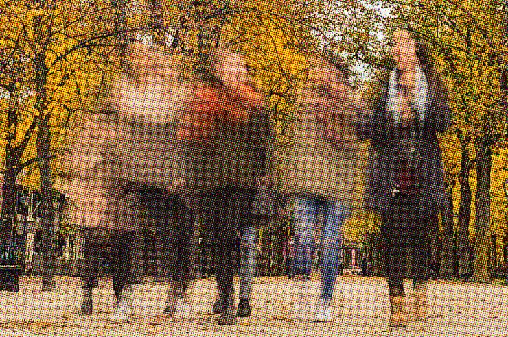 Motion blurred. Women walking down cobblestone path, wearing jackets and scarves, with fall colors and trees in the background.
