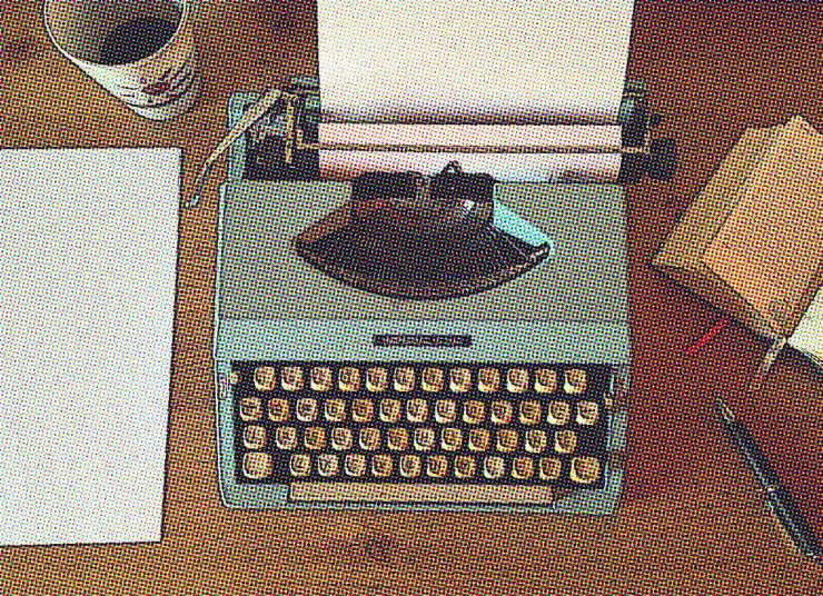 Blue vintage typewriter with blank paper in the center of frame, with coffee cup and black paper on the left, and open book and pen on the right.