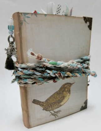 Image of junk journal with bird on front and twisted rope closure.