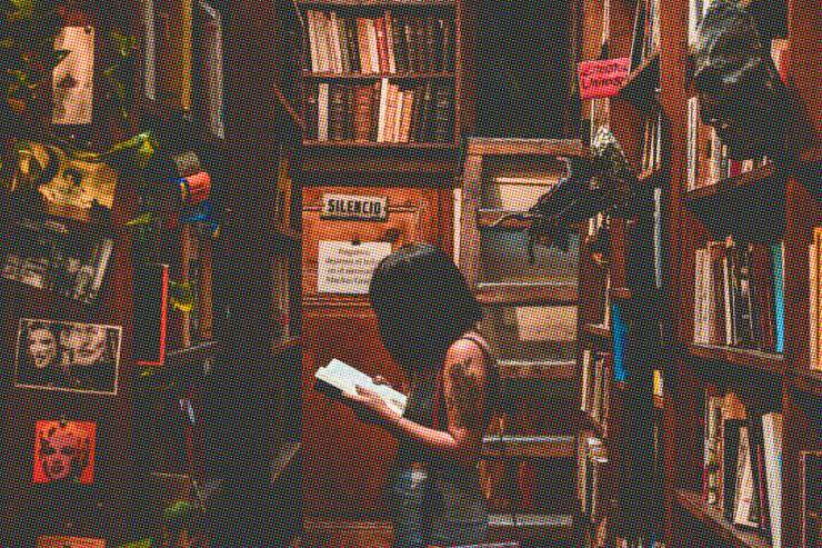 Person standing with open book in library.